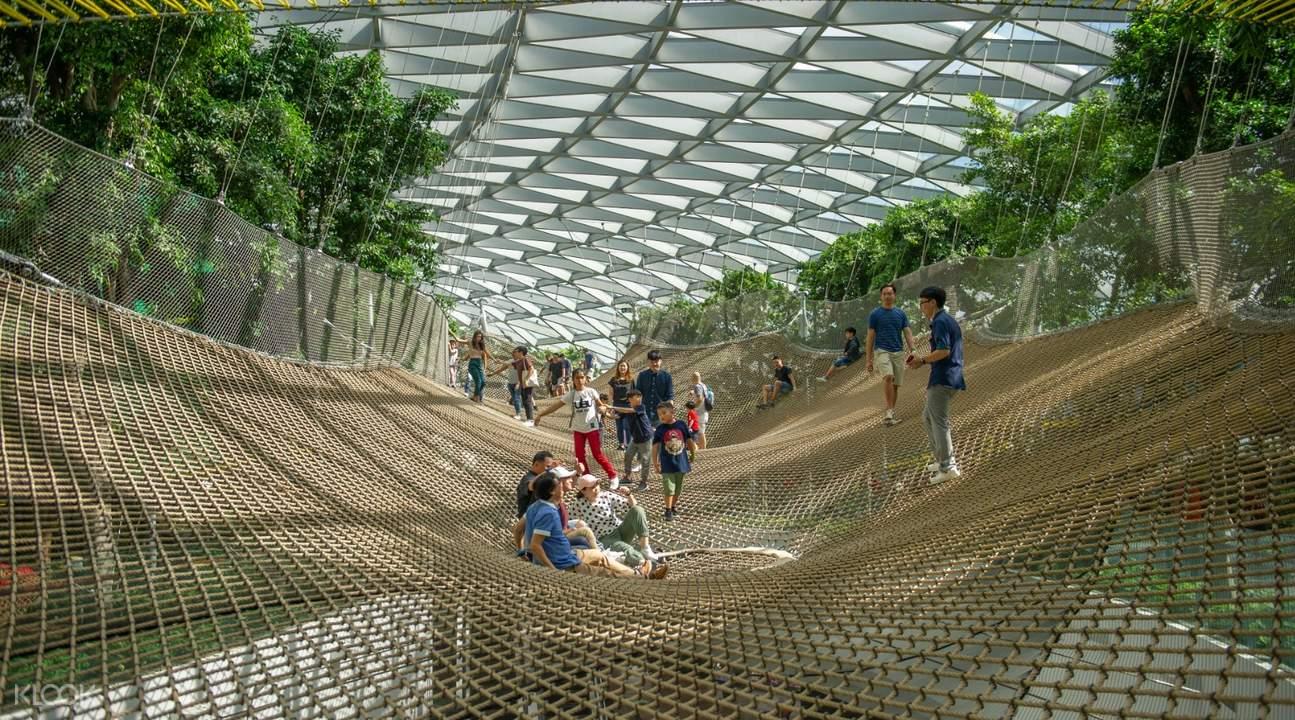 people walking around manulife sky nets in jewel changi airport singapore